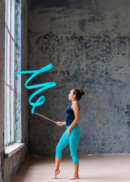 Giovane donna che fa ballo relativo alla ginnastica con il nastro blu Foto Gratuite