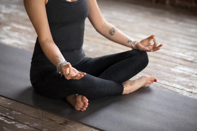 Giovane donna che fa esercitazione di sukhasana, fine in su Foto Gratuite