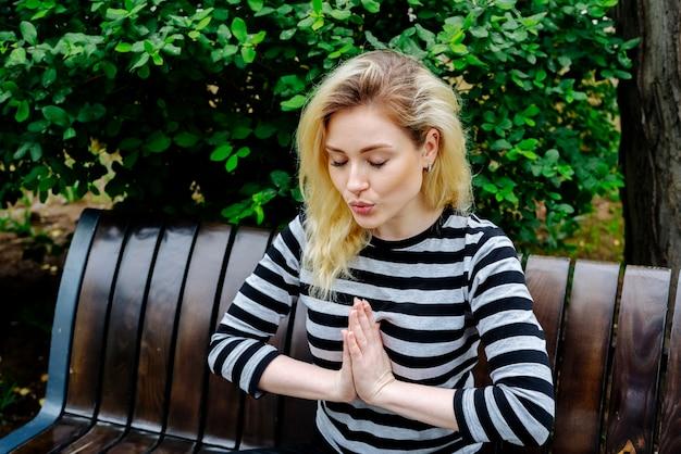 Giovane donna che fa esercizio e meditazione di yoga che si siedono su un banco in un parco nella cima a strisce Foto Gratuite