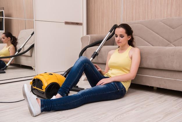 Giovane donna che fa pulizia a casa Foto Premium