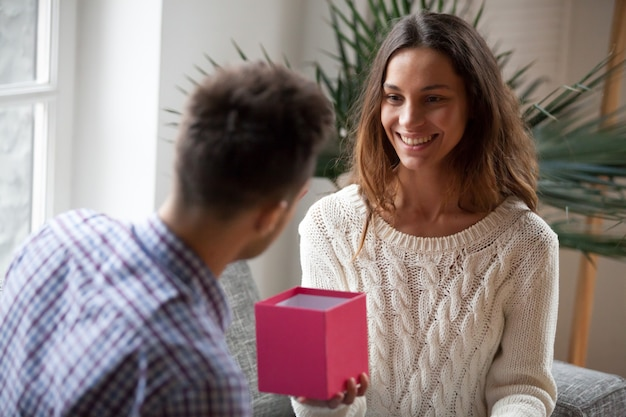 Giovane donna che fa regalo che dà regalo aperto al marito Foto Gratuite