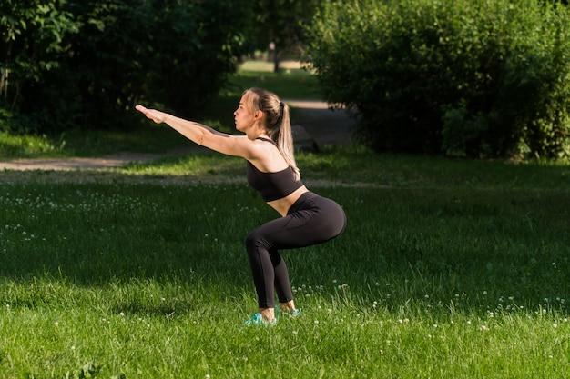Giovane donna che fa sport nel parco Foto Premium