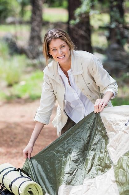 Giovane donna che fa tenda mentre il campeggio Foto Premium