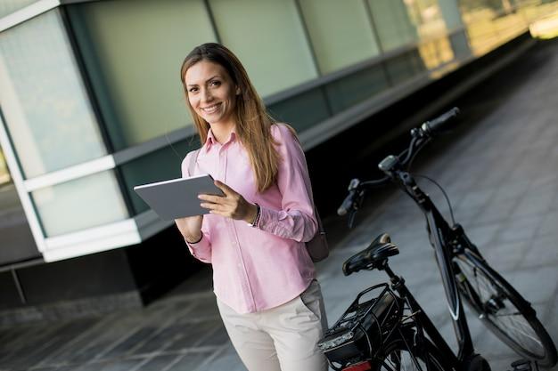 Giovane donna che fa una pausa una bicicletta elettrica e che utilizza compressa digitale nell'ambiente urbano Foto Premium