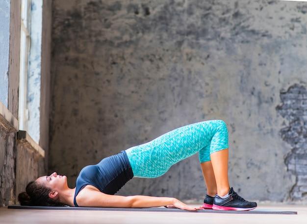 Giovane donna che fa yoga sul materassino Foto Gratuite