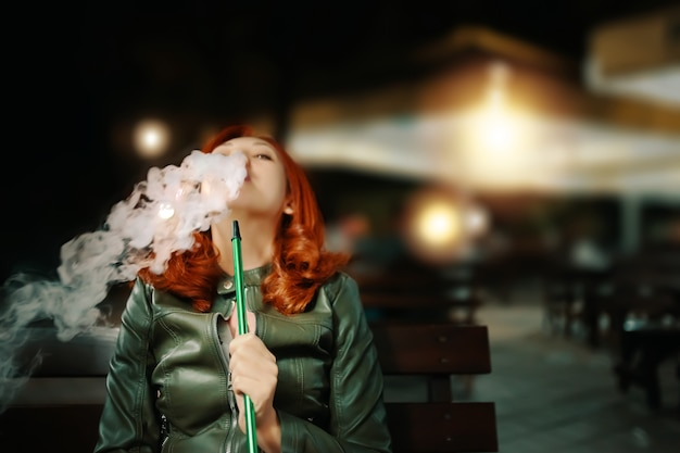Giovane donna che fuma narghilè al lounge bar Foto Premium