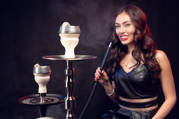 Giovane donna che fuma un narghilé su oscurità Foto Premium