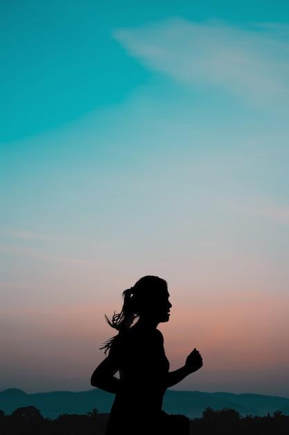 Giovane donna che funziona all'alba con lo sfondo naturale della montagna. Foto Premium