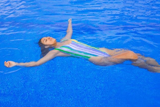 Giovane donna che galleggia in piscina Foto Premium