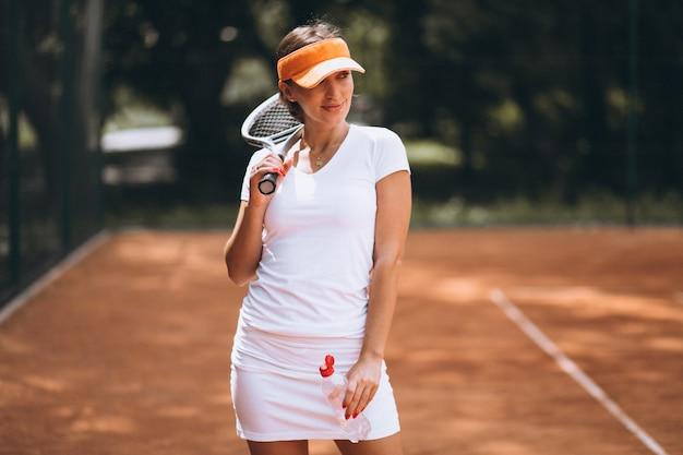 Giovane donna che gioca a tennis e acqua potabile alla corte Foto Gratuite