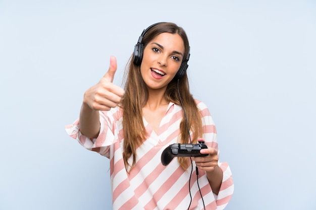 Giovane donna che gioca con un controller per videogiochi con il pollice in alto perché è successo qualcosa di buono Foto Premium