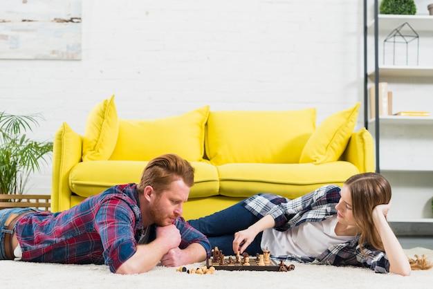 Giovane donna che gioca il gioco degli scacchi con il suo fidanzato Foto Gratuite