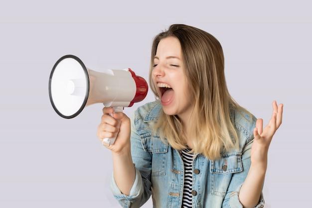 Giovane donna che grida su un megafono. Foto Premium