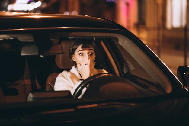 Giovane donna che guida in auto di notte Foto Gratuite