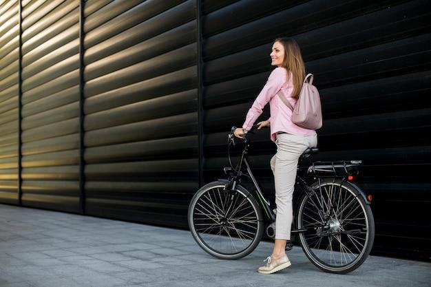 Giovane donna che guida una bicicletta elettrica nell'ambiente urbano Foto Premium