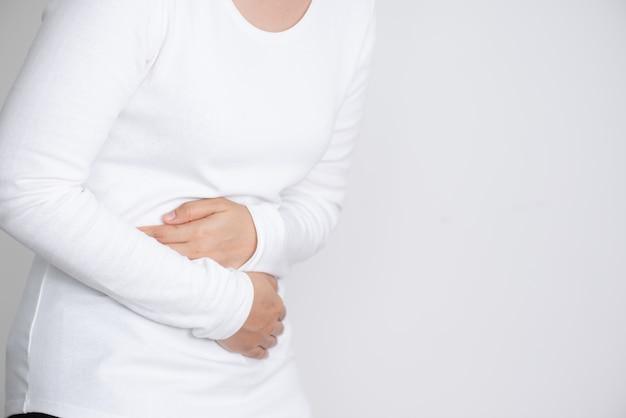 Giovane donna che ha mal di stomaco doloroso Foto Premium