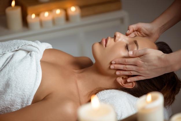 Giovane donna che ha massaggio viso rilassante nel salone spa. Foto Gratuite