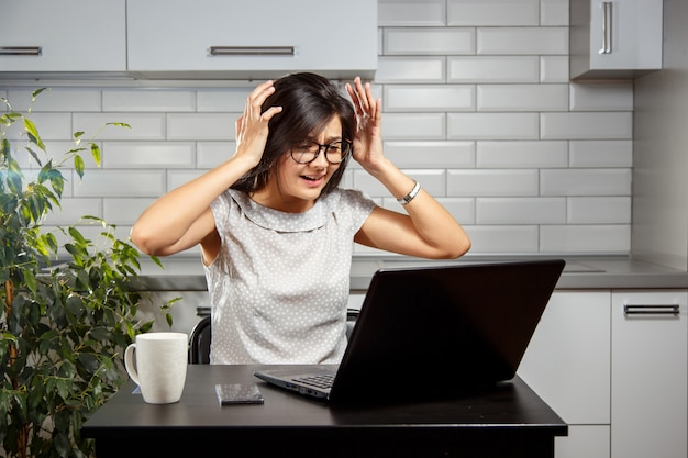 Giovane donna che ha problemi con il computer portatile Foto Premium