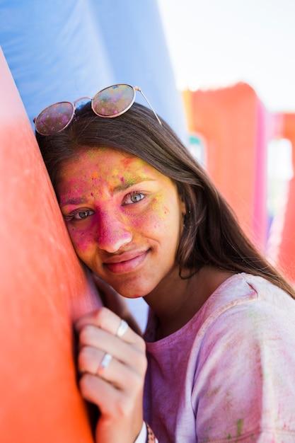 Giovane donna che indossa occhiali da sole con il viso coperto di colore holi rivolto verso l'obiettivo Foto Gratuite