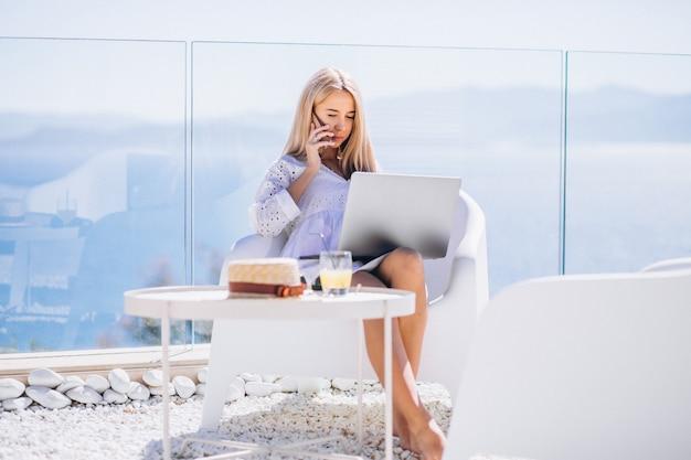Giovane donna che lavora al computer portatile in vacanza Foto Gratuite