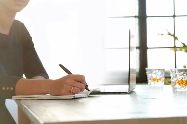 Giovane donna che lavora con il computer portatile e l'agenda Foto Gratuite