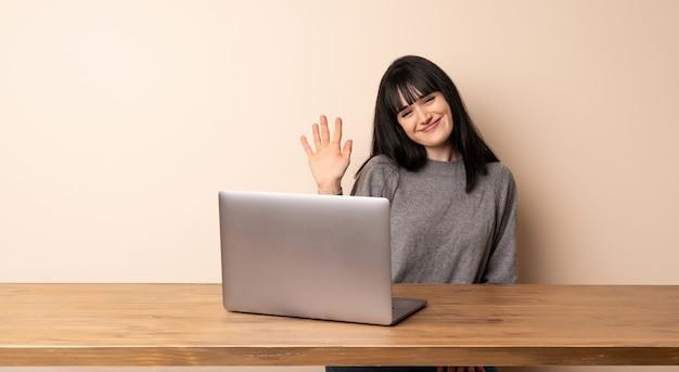 Giovane donna che lavora con il suo portatile salutando con la mano con l'espressione felice Foto Premium