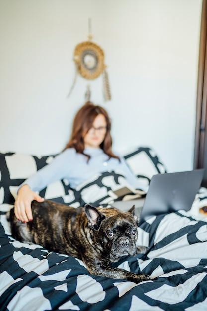 Giovane donna che lavora dal letto a casa con il computer. Foto Premium