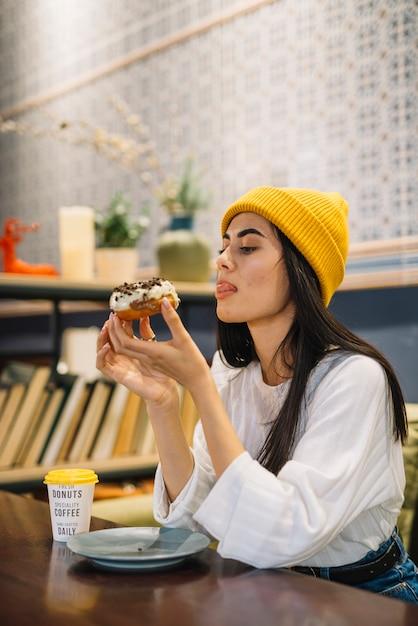 Giovane donna che lecca le labbra e che tiene dessert vicino alla tazza alla tavola Foto Gratuite