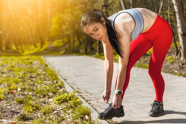 Giovane donna che lega la sua sneaker Foto Gratuite