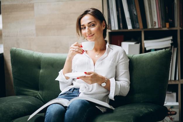 Giovane donna che legge un libro e che beve tè a casa Foto Gratuite