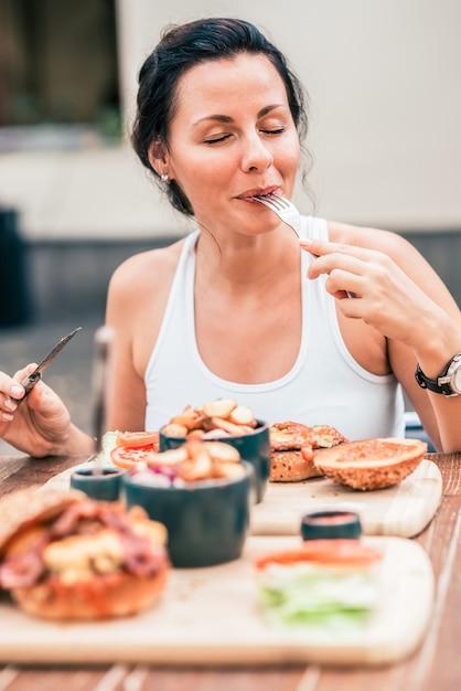 Giovane donna che mangia un pasto delizioso. Foto Premium