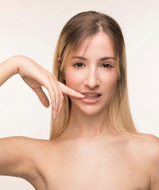 Giovane donna che morde la sua posa del chiodo Foto Gratuite