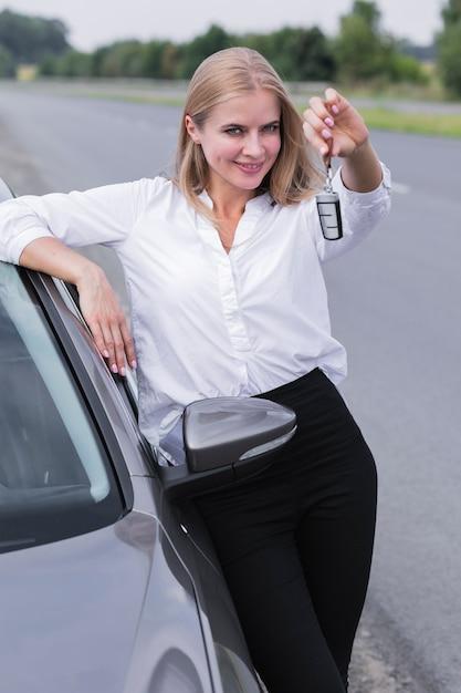 Giovane donna che mostra le chiavi al colpo medio dell'automobile Foto Gratuite
