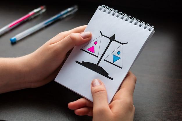 Giovane donna che mostra un blocco note con il concetto di uguaglianza di genere Foto Premium
