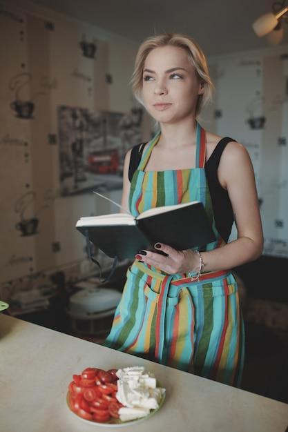 Giovane donna che osserva in su in un libro di ricette Foto Gratuite