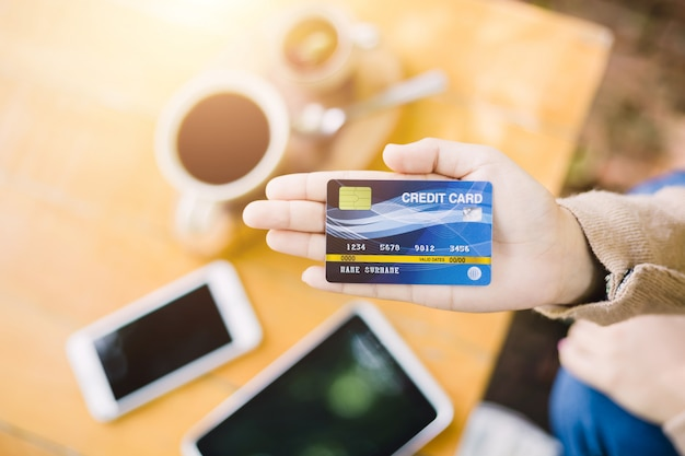 Giovane donna che paga per caffè con carta di credito Foto Premium