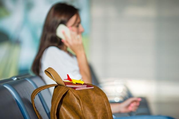 Giovane donna che parla al telefono mentre in attesa di imbarco Foto Premium