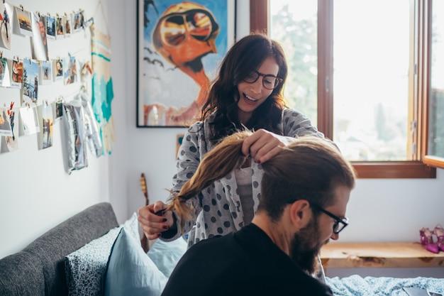 Giovane donna che pettina capelli della camera da letto domestica dell'interno dell'uomo barbuto Foto Premium