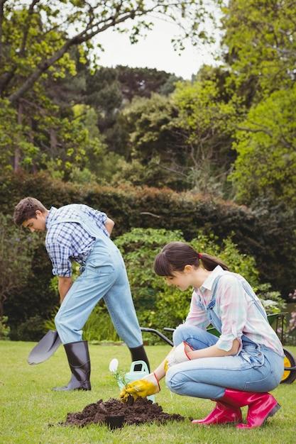 Giovane donna che pianta un alberello in giardino Foto Premium
