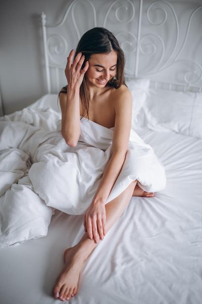 Giovane donna che posa nuda a letto Foto Gratuite