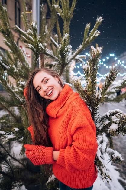 Giovane donna che posa vicino all'albero di natale sulla strada Foto Gratuite