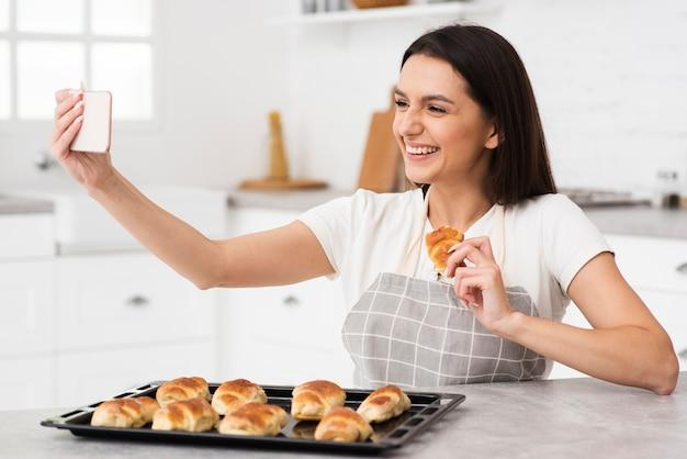 Giovane donna che prende un selfie in cucina Foto Gratuite