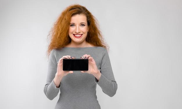 Giovane donna che presenta telefono Foto Premium