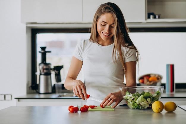 Giovane donna che produce insalata alla cucina Foto Gratuite