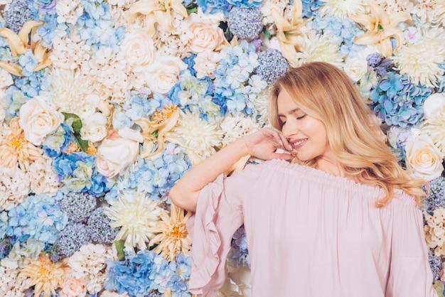 Giovane donna che propone sulla priorità bassa dei fiori Foto Gratuite
