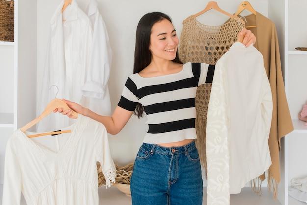 Giovane donna che prova sui vestiti Foto Gratuite