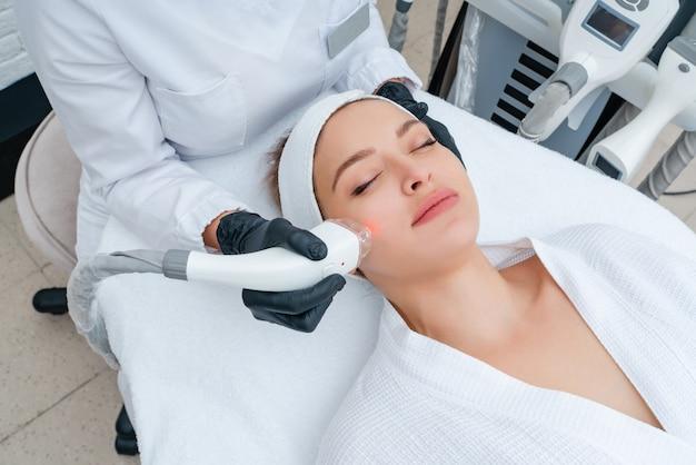 Giovane donna che riceve il trattamento laser nella clinica di cosmetologia Foto Premium