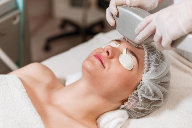 Giovane donna che riceve il trattamento laser Foto Premium
