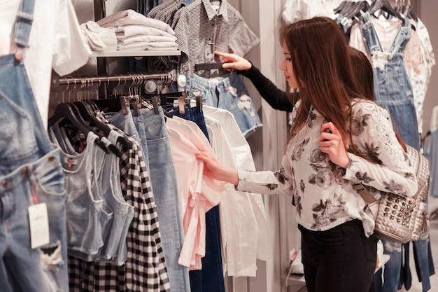 Giovane donna che sceglie i vestiti su una cremagliera in uno showroom. Foto Premium