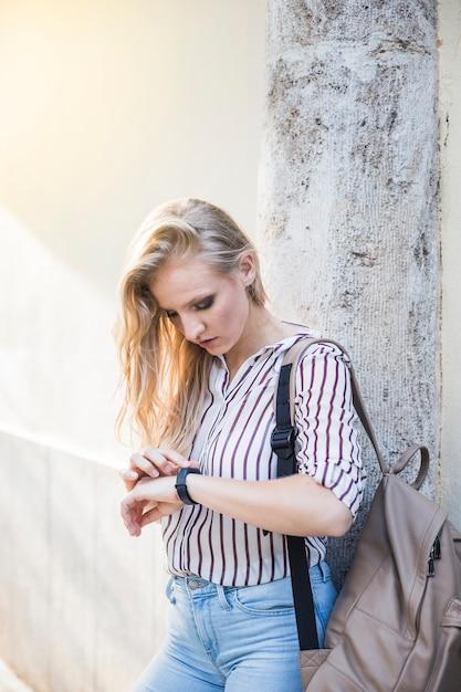 Giovane donna che si appoggia contro il muro guardando il tempo sull'orologio Foto Gratuite